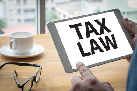 tax law: TAX LAW                Computing Computer  Laptop with screen on table Silhouette and filter sun Stock Photo