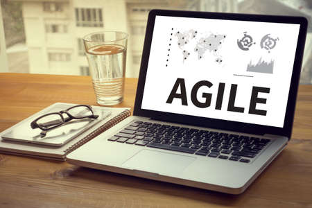 agile: Agile Agility Nimble Quick Fast Concept Computing Computer  Laptop with screen on table Silhouette and filter sun Stock Photo