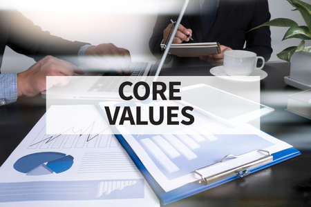 core strategy: CORE VALUES Image of man hand pointing at business document during discussion at meeting Stock Photo