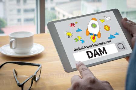 digital asset management: DAM Digital Asset Management Organization Computing Computer  Laptop with screen on table Silhouette and filter sun