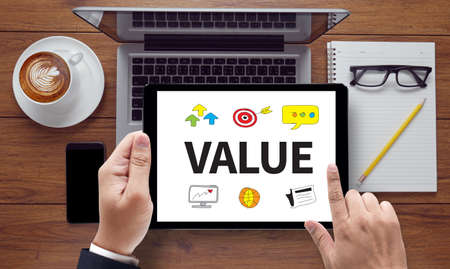 valuation: Value , on the tablet pc screen held by businessman hands - online, top view Value