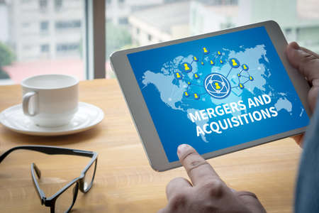 mergers: M&A (MERGERS AND ACQUISITIONS) Computing Computer  Laptop with screen on table Silhouette and filter sun Stock Photo