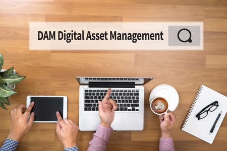 digital asset management: DAM Digital Asset Management Organization Two Businessman working at office desk and using a digital touch screen tablet and use computer Stock Photo