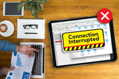 interrupted: computer Interrupted  Attention Alert Connection Interrupted Warning  Businessman working at office desk and using computer and objects, coffee, top view,