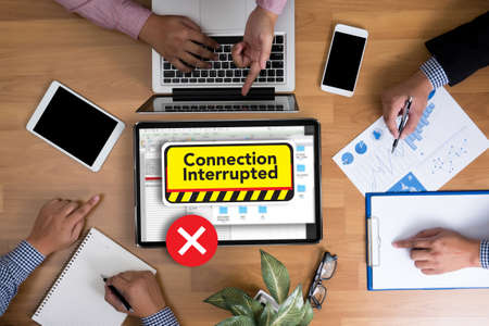 interrupted: computer Interrupted  Attention Alert Connection Interrupted Warning  Business team hands at work with financial reports and a laptop, top view