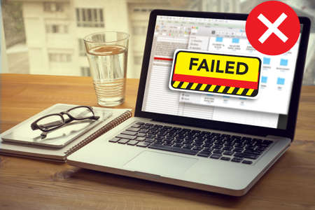 failing: NOT good Failed Fail Failing Fiasco Inability Unsuccessful it Failed Computing Computer  Laptop with screen on table Silhouette and filter sun Stock Photo