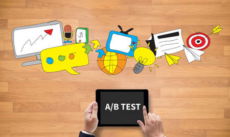 randomized: AB TEST, on the tablet pc screen held by businessman hands - online, top view