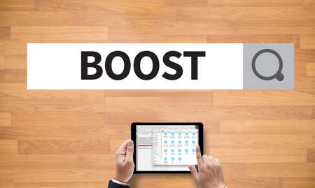 boost: BOOST YOUR BUSINESS, on the tablet pc screen held by businessman hands - online, top view Stock Photo