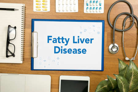 fatty liver: Fatty  Liver  Disease Professional doctor use computer and medical equipment all around, desktop top view Stock Photo