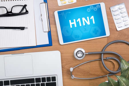 h1n1 vaccination: H1N1 Professional doctor use computer and medical equipment all around, desktop top view Stock Photo