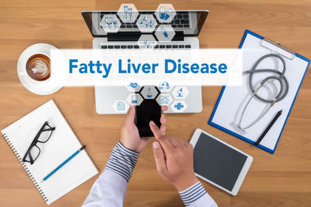 fatty liver: Fatty  Liver  Disease Doctor working at office desk and using a mobile touch screen phone, computer and medical equipment all around, top view, coffee Stock Photo