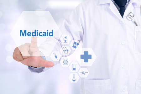 medicaid: Medicaid Medicine doctor working with computer interface as medical Stock Photo
