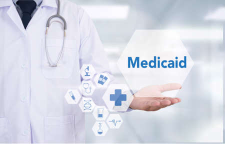 medicaid: Medicaid Medicine doctor hand working  Professional doctor use computer and medical equipment all around, desktop top view Stock Photo