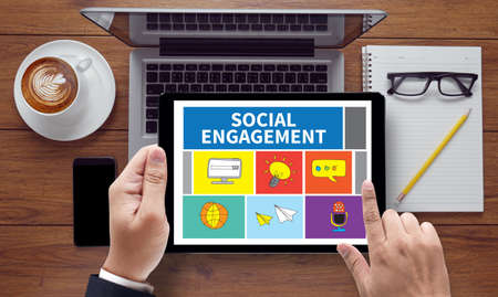 participatory: SOCIAL ENGAGEMENT, on the tablet pc screen held by businessman hands - online, top view Stock Photo