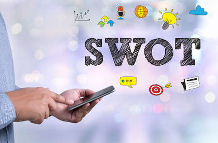 SWOT person holding a smartphone on blurred cityscape background Stock Photo