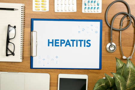 remission: HEPATITIS  Professional doctor use computer and medical equipment all around, desktop top view