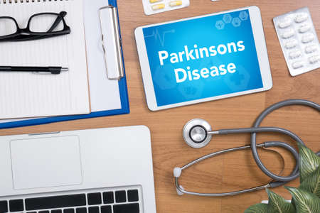 parkinson's disease: Parkinsons Disease Professional doctor use computer and medical equipment all around, desktop top view