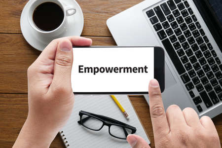 enabling: Empowerment message on hand holding to touch a phone, top view, table computer coffee and book Stock Photo