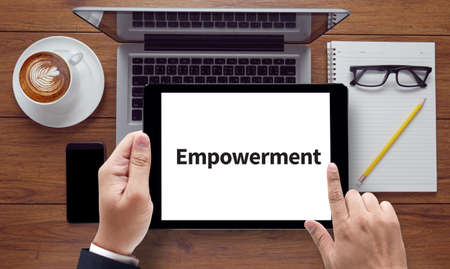 enabling: Empowerment, on the tablet pc screen held by businessman hands - online, top view Stock Photo