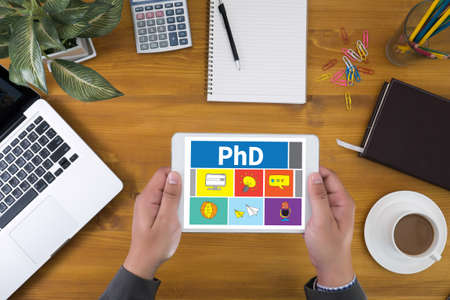 funding of science: PhD Doctor of Philosophy Degree Education Graduation Corporate identity mock up on an hardwood desk with laptop, tablet, smartphone and a cup of coffee, top view Stock Photo