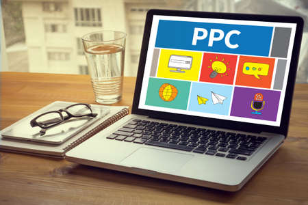 adwords: PPC - Pay Per Click concept Computing Computer  Laptop with screen on table Silhouette and filter sun