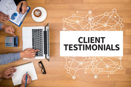 testimony: CLIENT TESTIMONIALS Business team hands at work with financial reports and a laptop Stock Photo