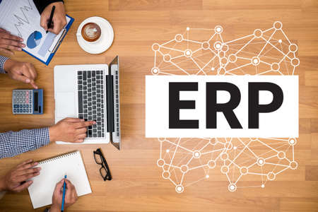 ENTERPRISE RESOURCE PLANNING (ERP)Business team hands at work with financial reports and a laptop