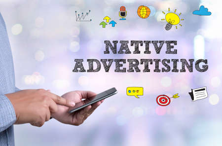 NATIVE ADVERTISING person holding a smartphone on blurred cityscape background Stock Photo