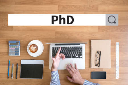 funding of science: PhD Doctor of Philosophy Degree Education Graduation Businessman working with financial reports and a laptop with other objects around, coffee,  top view