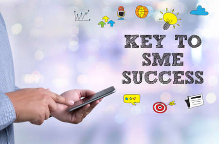 enterprises: KEY TO SME SUCCESS  Small and medium-sized enterprises person holding a smartphone on blurred cityscape background Stock Photo