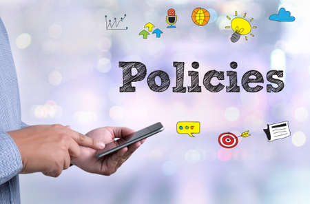 principle: Policies                     Privacy Policy Information Principle Strategy Rules person holding a smartphone on blurred cityscape background