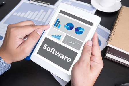 doing business: Software Data Digital Programs System Technology computer Modern people doing business, graphs and charts being demonstrated on the screen of a touch-pad,blank screen copy space Stock Photo