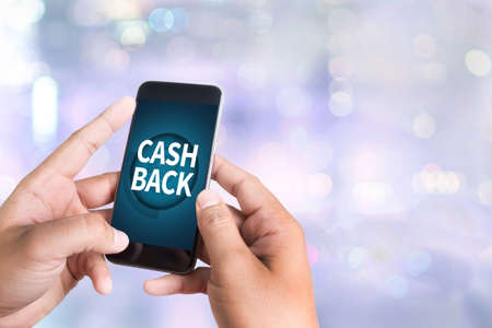 CASH BACK person holding a smartphone on blurred cityscape background