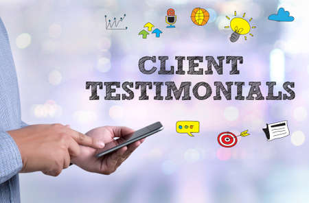 testimonials: CLIENT TESTIMONIALS person holding a smartphone on blurred cityscape background Stock Photo