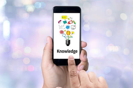 insights: Knowledge   Expertise Intelligence Learn Knowledge person holding a smartphone on blurred cityscape background Stock Photo