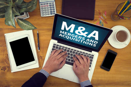 company merger: M&A (MERGERS AND ACQUISITIONS) Corporate identity mock up on an hardwood desk with laptop, tablet, smartphone and a cup of coffee, man working Stock Photo