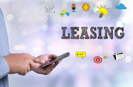 LEASING person holding a smartphone on blurred cityscape background Stock Photo