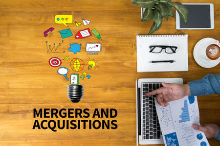acquiring: M&A (MERGERS AND ACQUISITIONS) Businessman working at office desk and using computer and objects, coffee, top view, with copy space Stock Photo