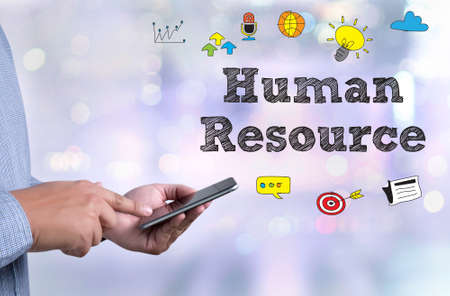 HRM Human Resource Management  Strategy Planning Working HRM man person holding a smartphone on blurred cityscape background Stock Photo