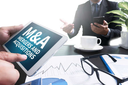 mergers: M&A (MERGERS AND ACQUISITIONS) Businessman pointing at touchpad with data, tablet with isolated screen