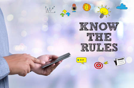 KNOW THE RULES person holding a smartphone on blurred cityscape background Stock Photo