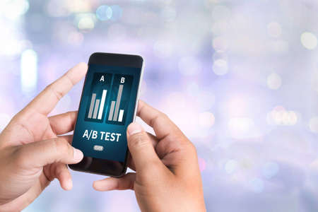 hipotesis: AB TEST person holding a smartphone on blurred cityscape background