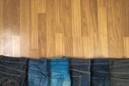 jeanswear: Blue jeans on a brown wooden background and Blue jeans denim Collection jeans stacked