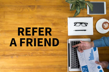 refer: REFER A FRIEND Businessman working at office desk and using computer and objects, coffee, top view Stock Photo