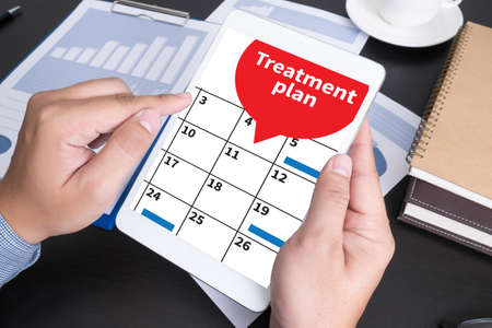 doing business: Treatment plan Modern people doing business, graphs and charts being demonstrated on the screen of a touch-pad,blank screen copy space Stock Photo