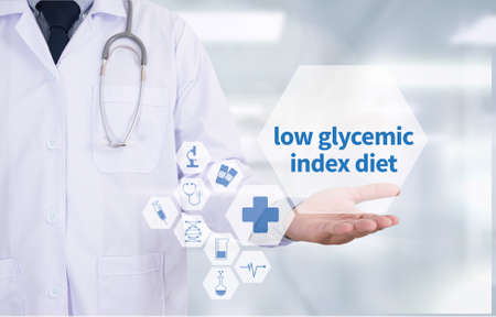 hypoglycaemia: low glycemic index diet Medicine doctor hand working  Professional doctor use computer and medical equipment all around, desktop top view Stock Photo