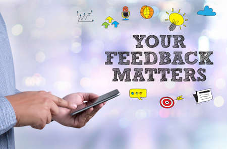 criticism: YOUR FEEDBACK MATTERS person holding a smartphone on blurred cityscape background