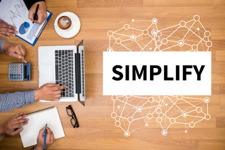pragmatic: SIMPLIFY Business team hands at work with financial reports and a laptop
