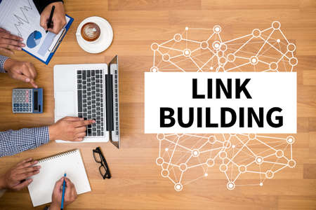 link building: LINK BUILDING Business team hands at work with financial reports and a laptop Stock Photo
