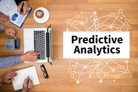 Predictive Analytics Business team hands at work with financial reports and a laptop